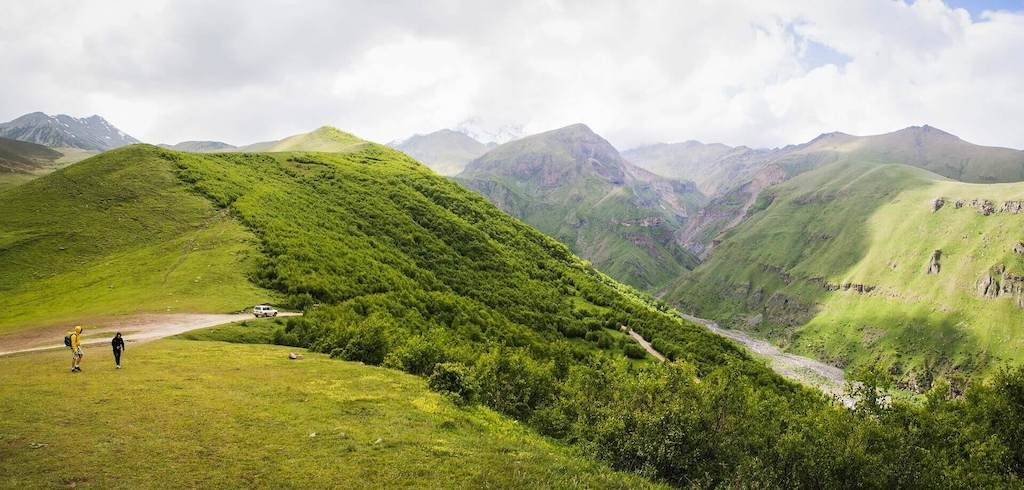 Groene bergen in het Kazbegi National Park met backpackers in Georgië