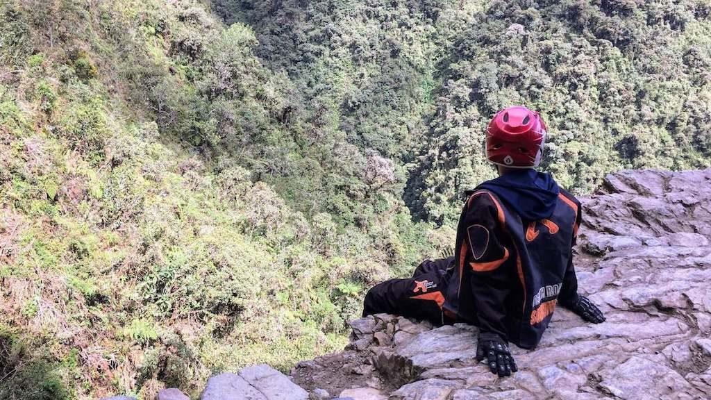 Backpacker met helm kijkt in de afgrond van de Death Road in Bolivia