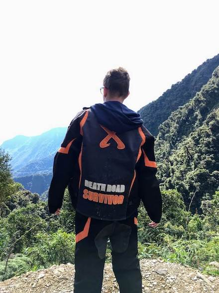 Mountainbiker kijkt uit over de bergen langs de Death Road in Bolivia