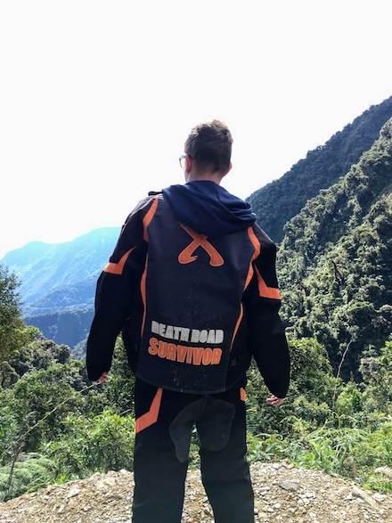 Mountainbiker kijkt uit over de bergen langs de Death Road in Bolivia