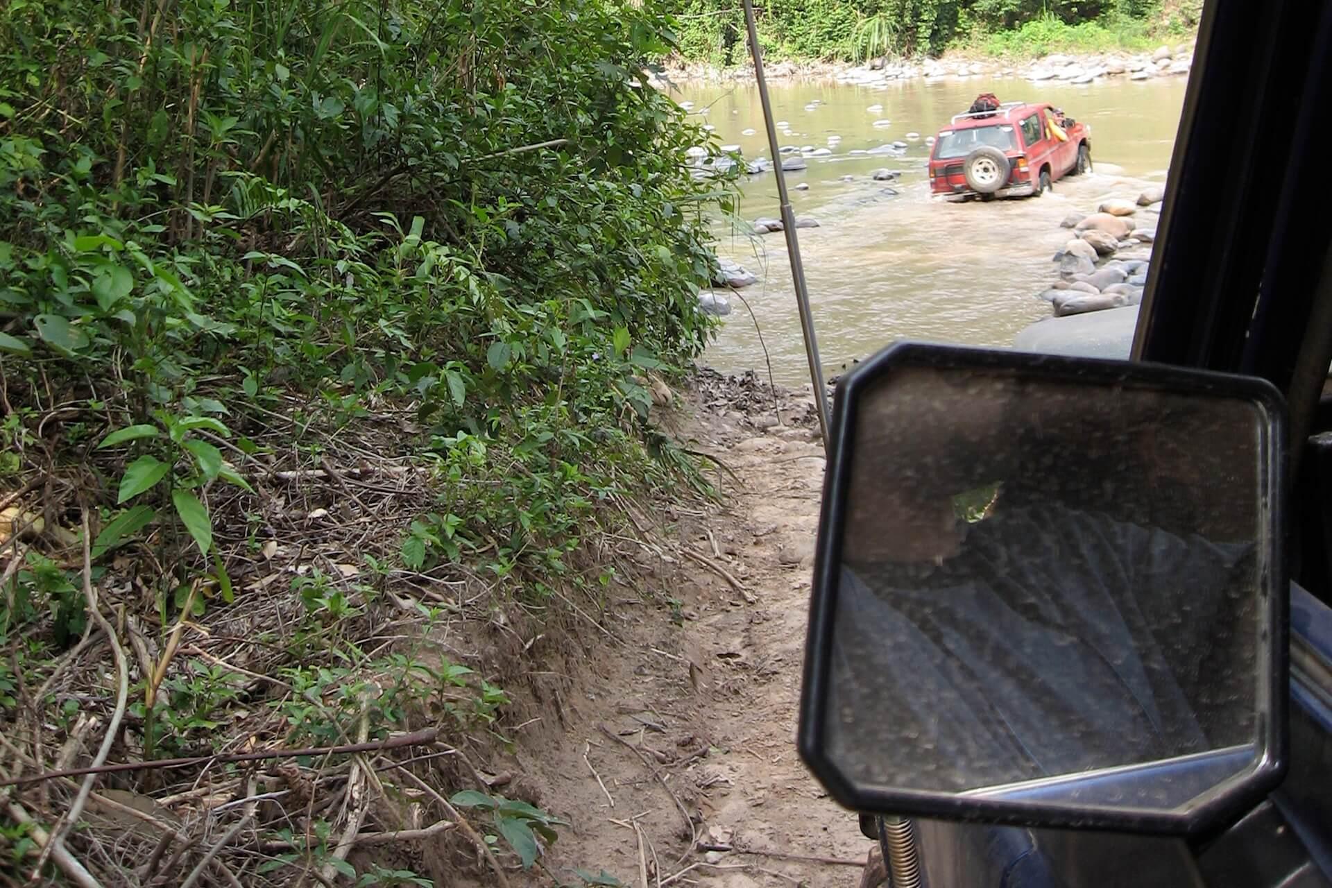Een 4x4 gaat door een rivier in het Amboro National Park in Bolivia