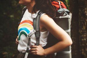 Vrouwelijke backpacker met backpack en shirt met regenboog