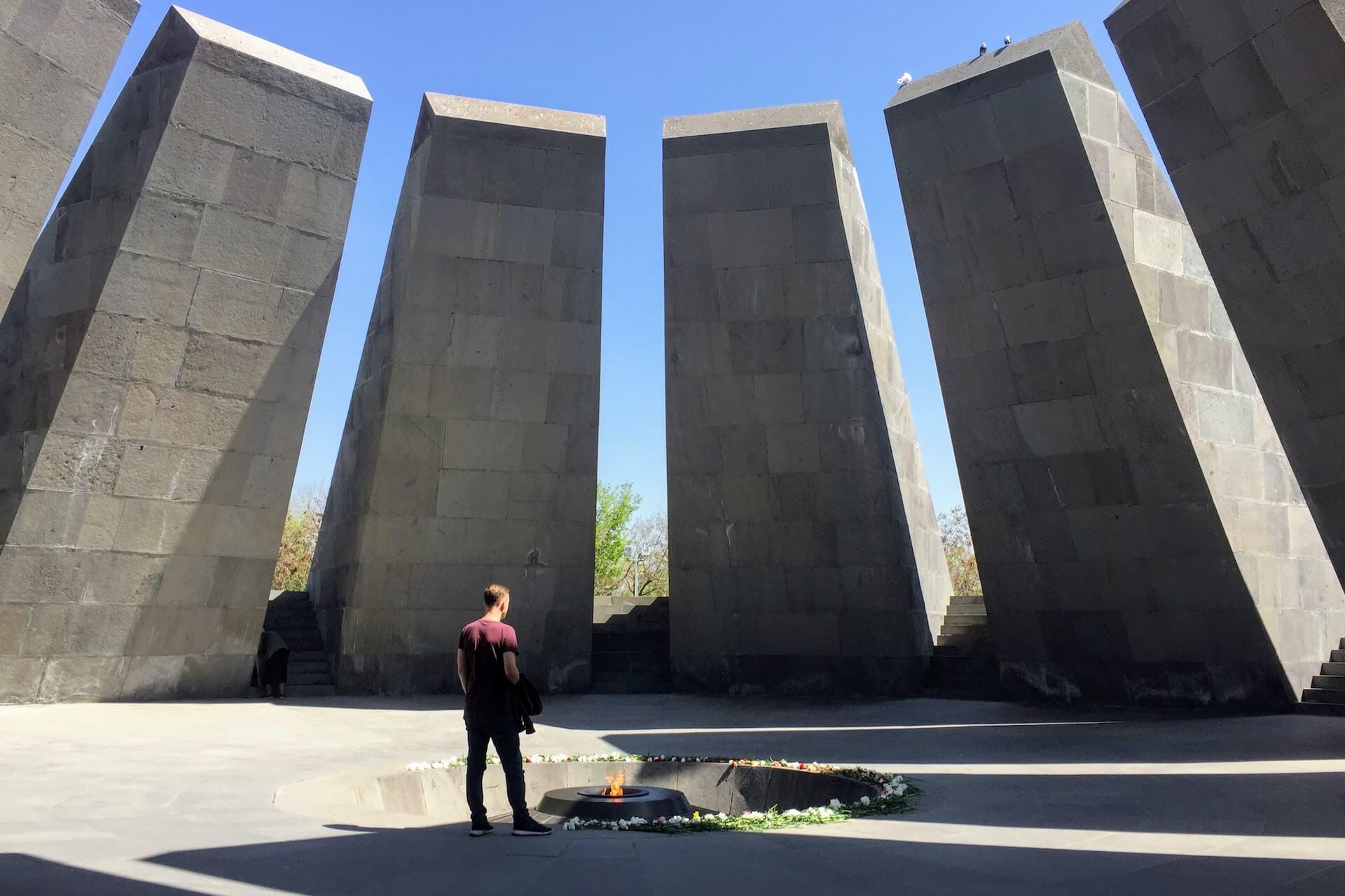Mannelijke backpacker kijkt naar het brandende vuur van het Armenian Genocide Memorial in Jerevan