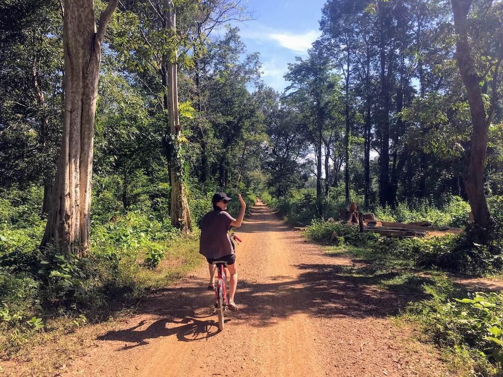Vrouwelijke backpacker zwaait vanaf een fiets op het eiland Don Det in Laos