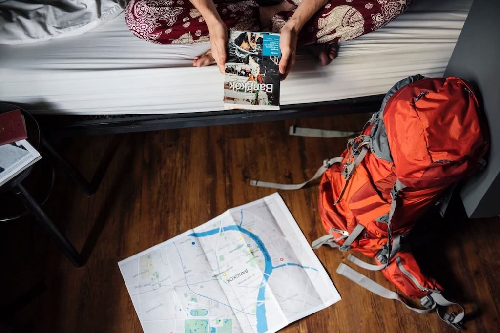 Backpacker met Lonely Planet, kaart en backpack voor backpacken bespaartips
