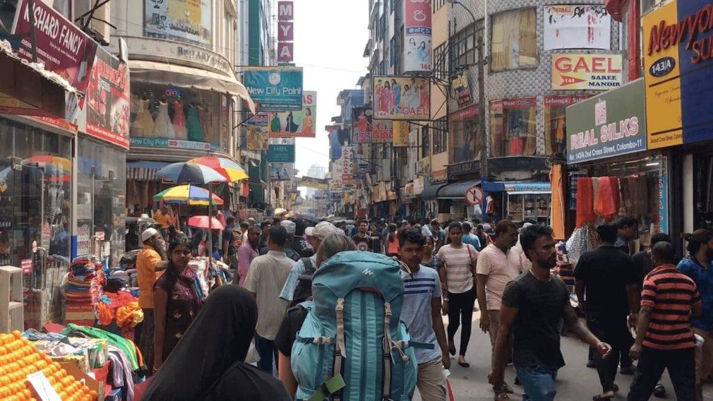 Vrouwelijke backpacker loopt over de markt in Colombo in Sri Lanka.