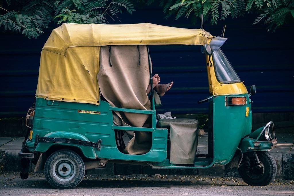 Man slaapt in groene tuktuk