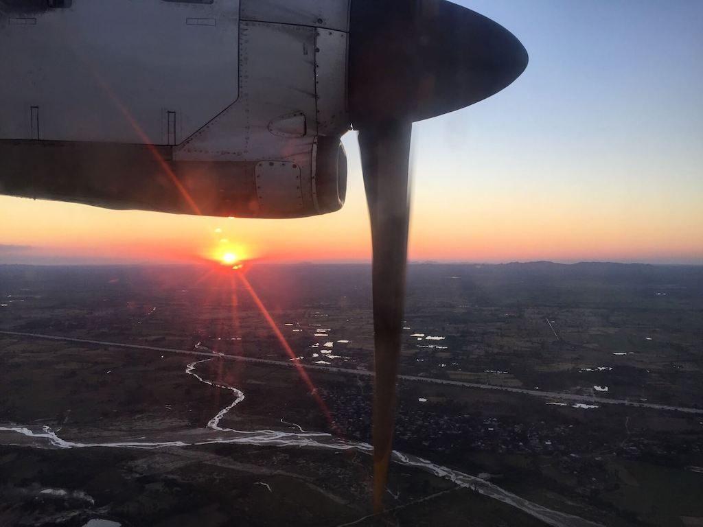 Vliegtuig met een ondergaande zon boven Myanmar