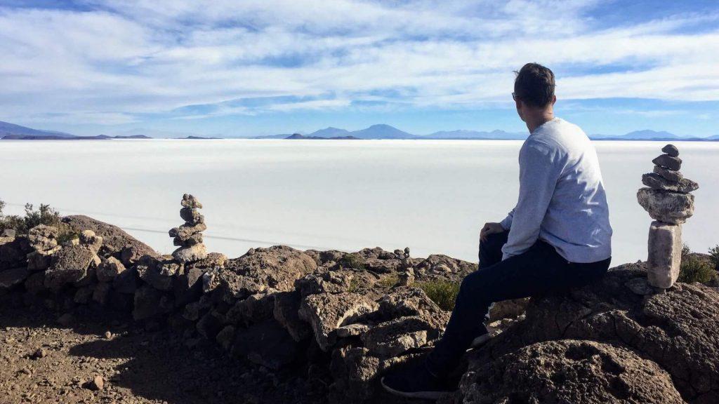 Mannelijke backpacker kijkt uit over de zoutvlakte van Uyuni in Bolivia