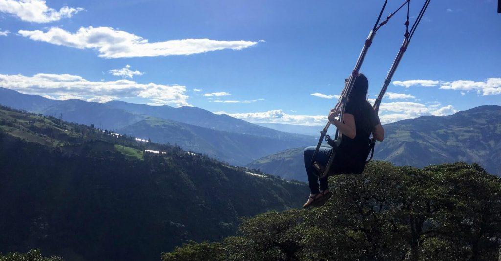 Backpacker zit op schommel bij Casa del Arbol in Banos, Ecuador