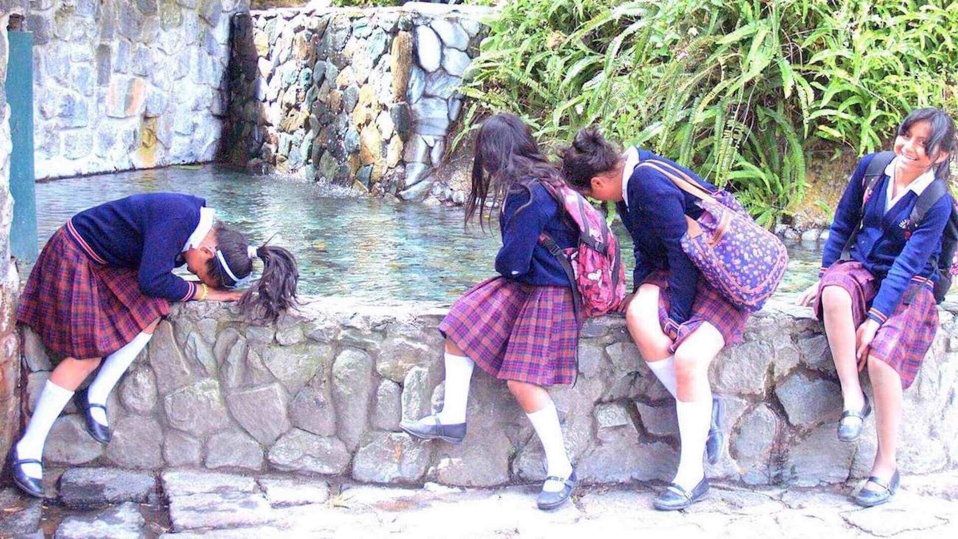Meisjes in uniformen bij een waterval in Banos, Ecuador