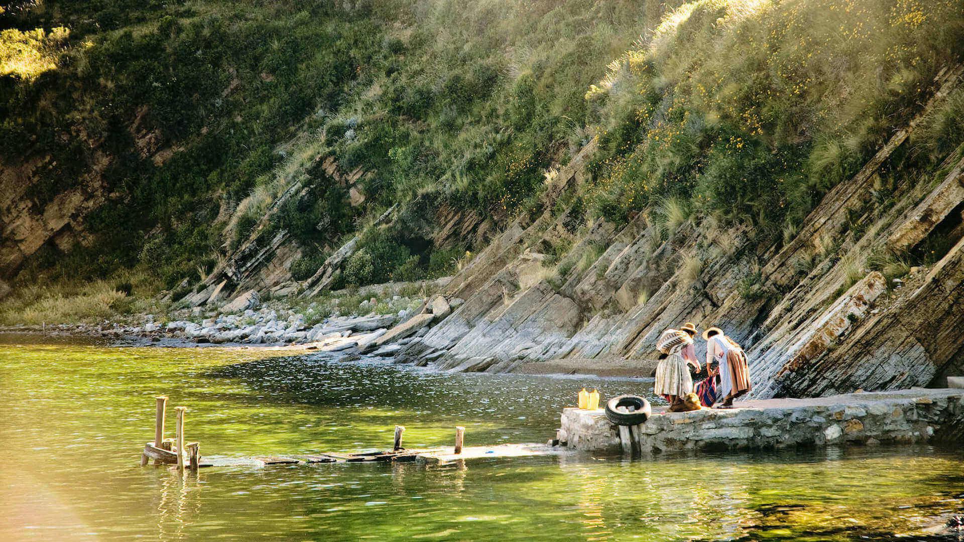Twee Boliviaanse vrouwen wassen kleding op Isla del Sol in Bolivia