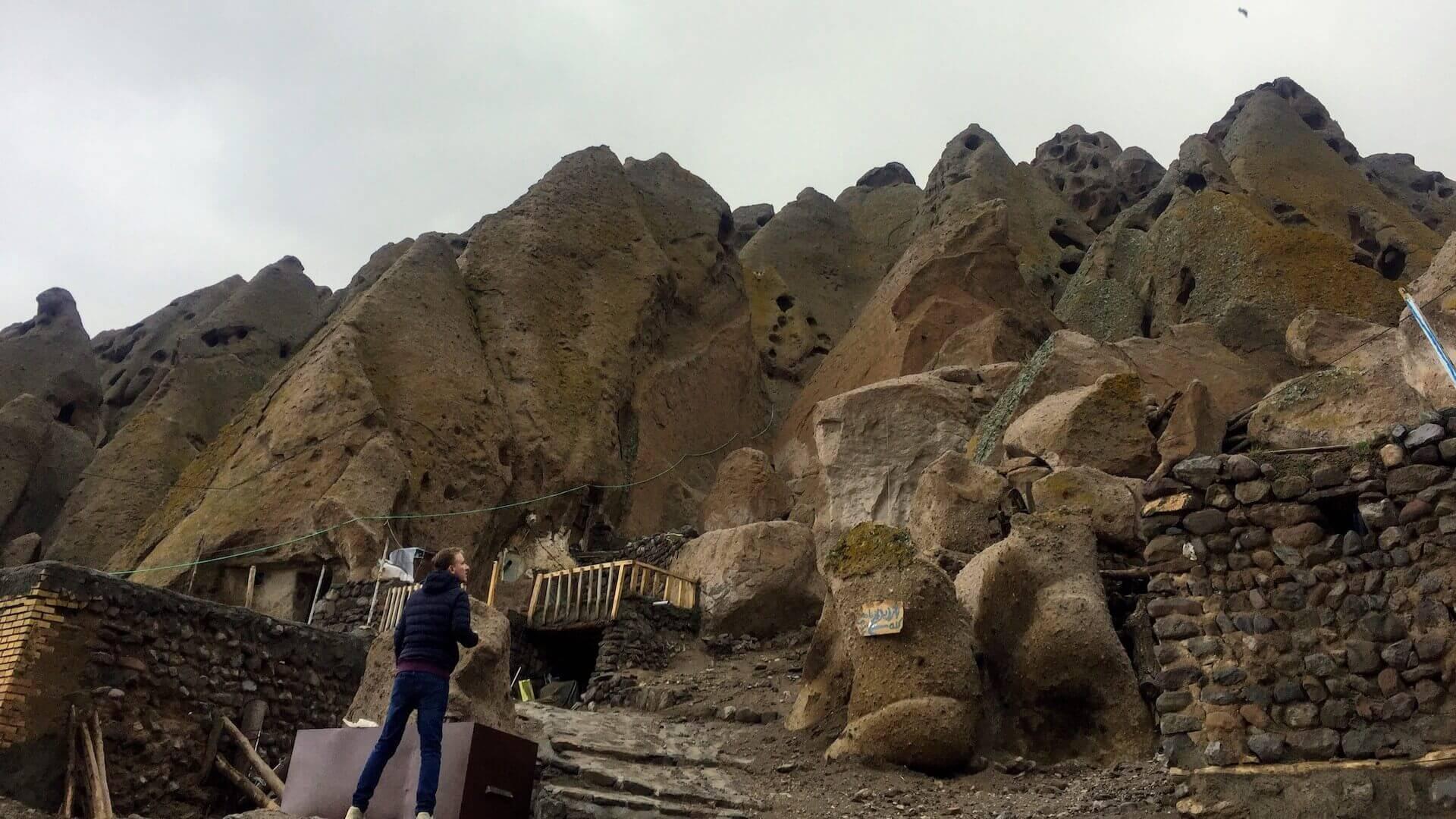 Mannelijke backpacker kijkt uit over de rotswoningen van Kandovan in Iran