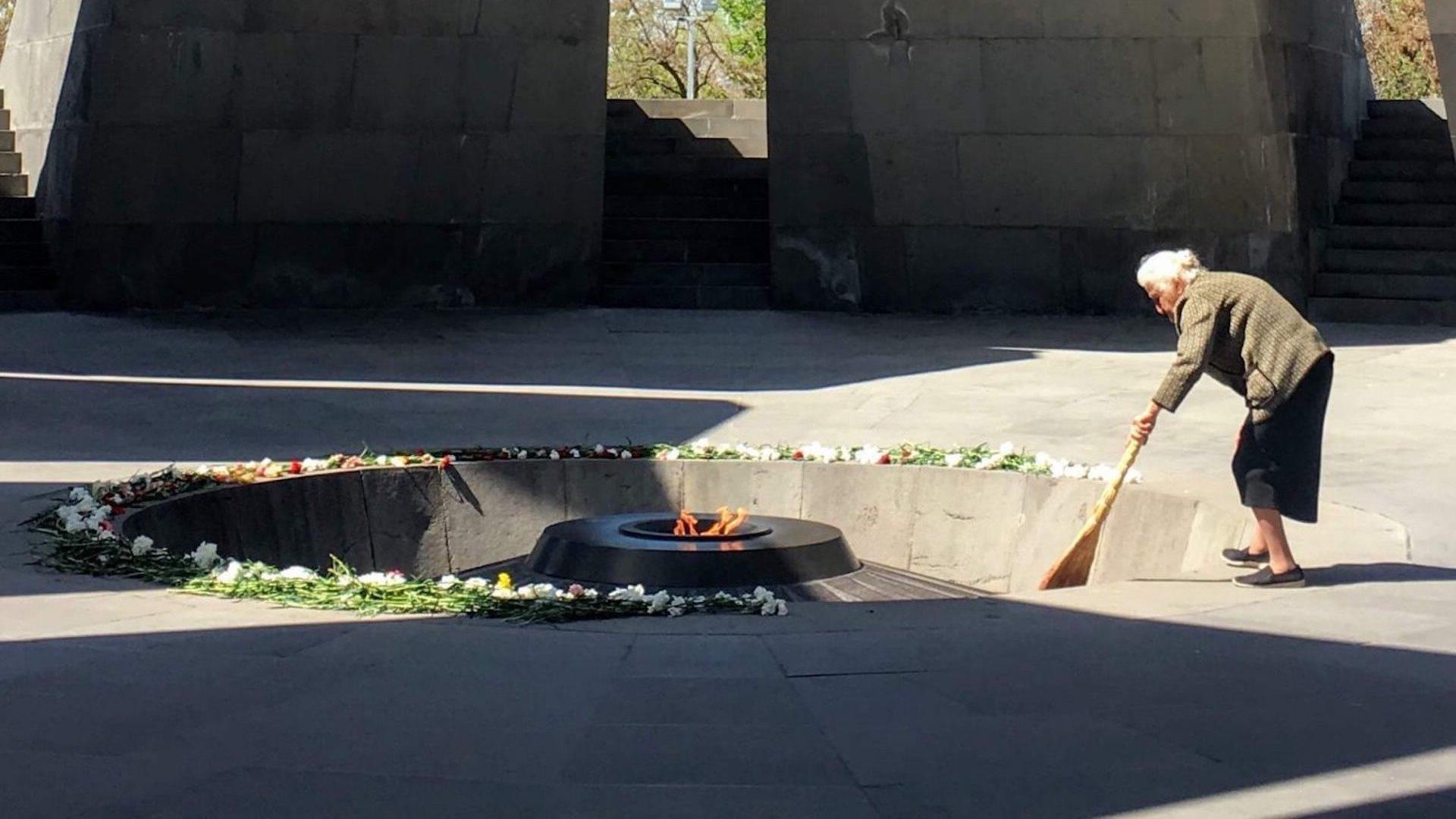 Oud vrouwtje maakt schoon bij de Armenian Genocide Memorial in Jerevan