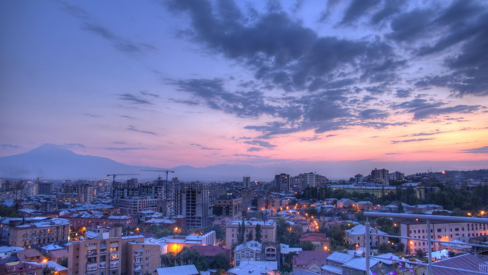 Zicht op de skyline en de ondergaande zon in Jerevan