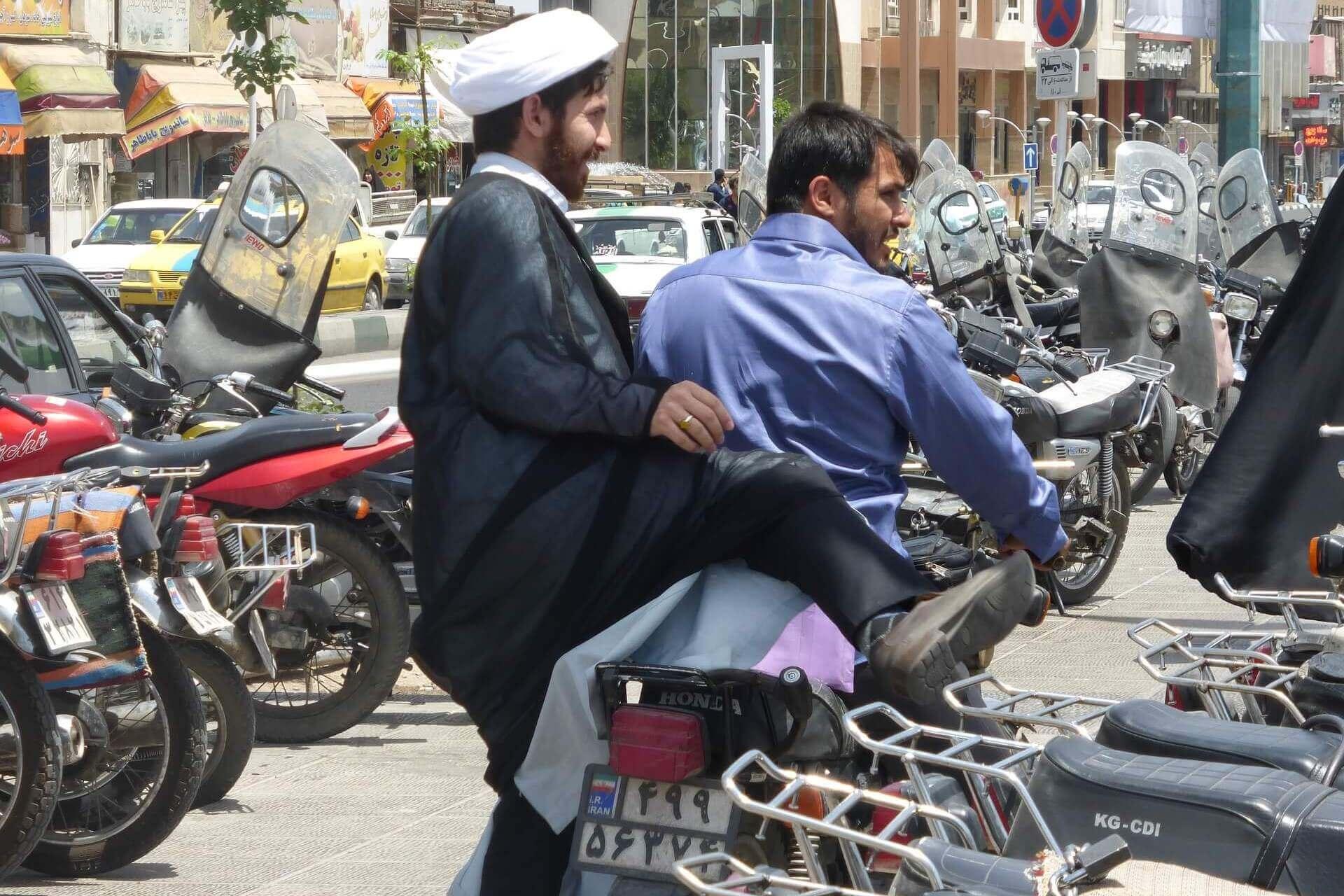 Twee Iraanse mannen op een scooter in Qom