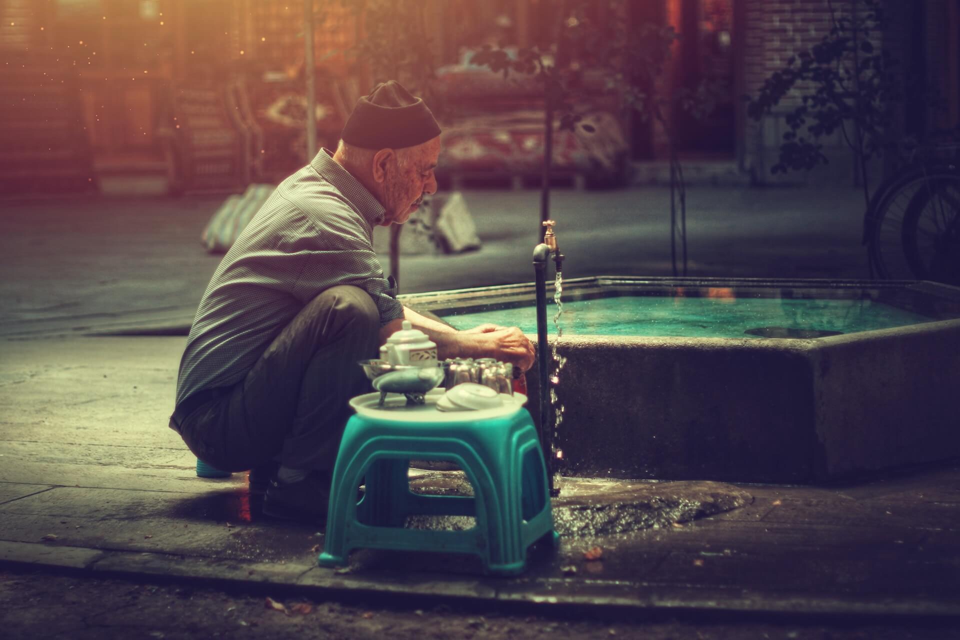 Oude man wast zijn handen in de Bazaar van Tabriz in Iran