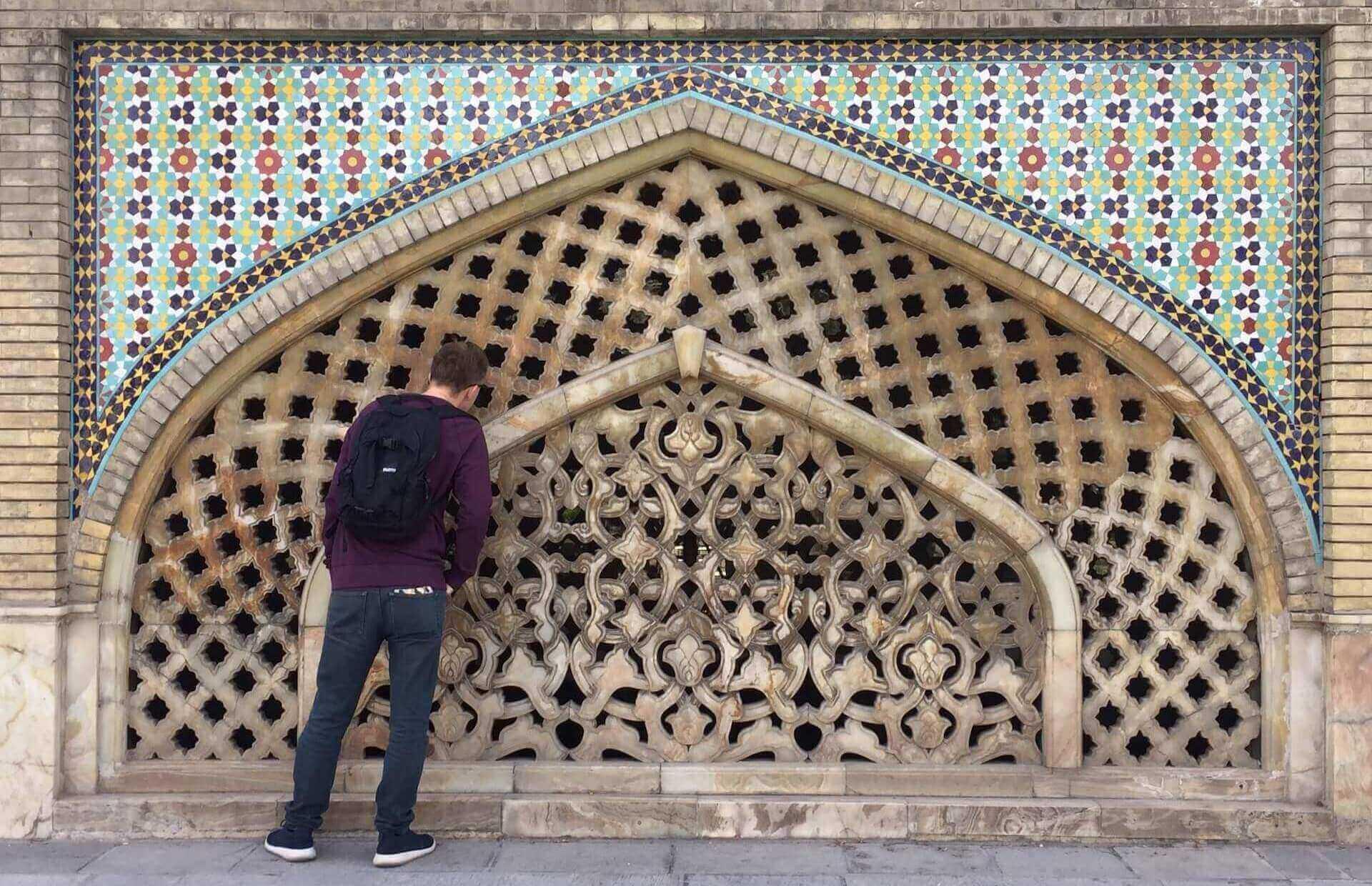 Man met backpack kijkt naar details in het Golestan Paleis in Teheran