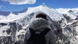 Vrouwelijke backpacker kijkt uit over de bergen bij skigebied Gudauri in Georgië