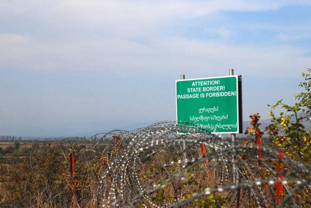 Prikkeldraad en een verboden bord bij de grens met Zuid-Ossetië in Georgië