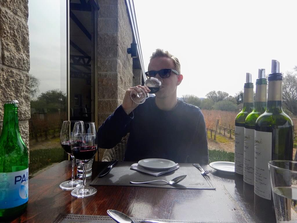 Mannelijke backpacker drinkt Argentijnse wijn bij de Bodega Colome
