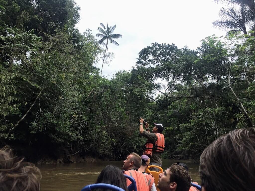 Een gids probeert wild te spotten op een boot in de Cuyabeno Wildlife Reserve
