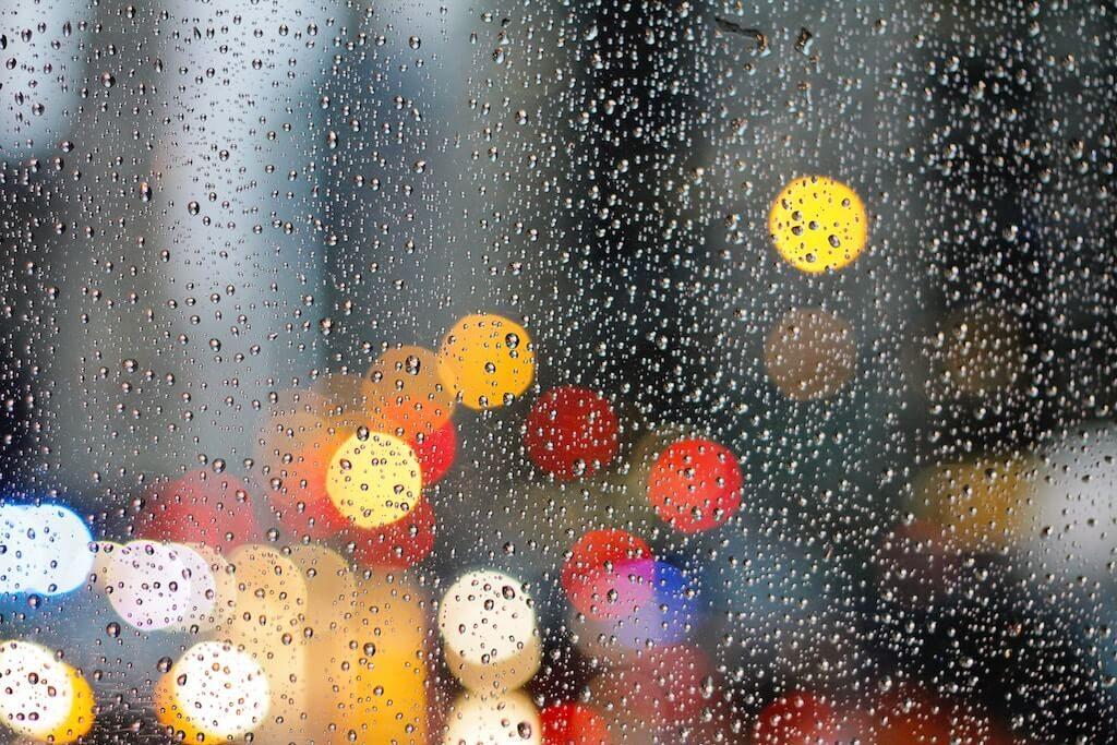 Lichtjes achter een ruit met regendruppels